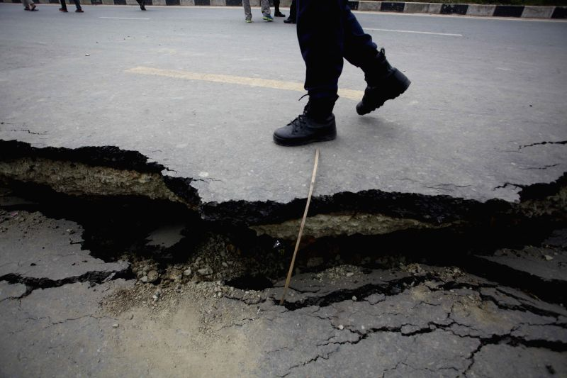 A man passes through a damaged road in Bhaktapur, Nepal, April 26, 2015. A total of 3,218 people had been killed and about 6,500 others injured in the powerful ...