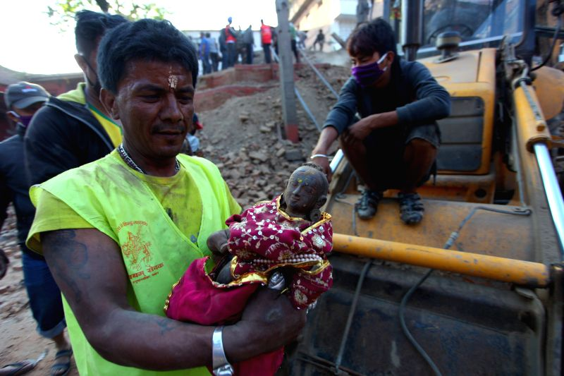 A member of a rescue team take the idol of Goddess Radha to a safe place from a fallen temple at Hanuman Dhoka Durbar Square after the massive earthquake in ...