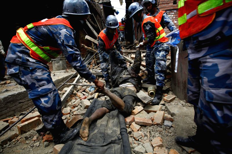 Members of the Nepalese Armed Police Force carry the body of a victim from a house in Bhaktapur, Nepal, April 26, 2015. A total of 3,218 people were killed and ...