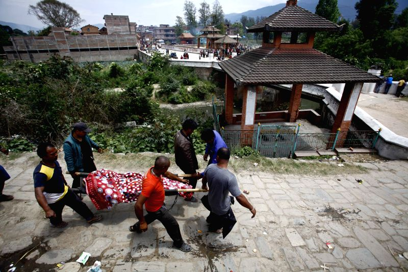 People carry the body of a victim in Bhaktapur, Nepal, April 26, 2015. A total of 3,218 people had been killed and about 6,500 others injured in the powerful ...