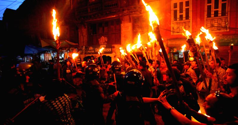 Police stop demonstrators during a torch rally on the eve of a three-day general strike called by the UCPN (Maoist)-led 30-party alliance in Kathmandu, Nepal, ...