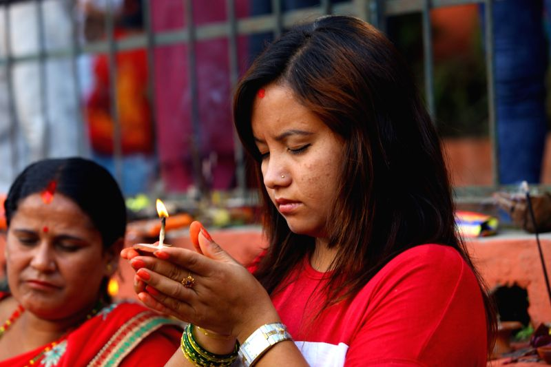 A woman prays with lighting butter lamp while offering her prayers celebrating Nag Panchami, the snake day festival, in Kathmandu, Nepal, on Aug. 1, 2014. The ...