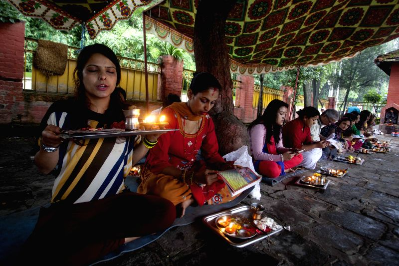 Hindu women read holy books and pray on the occasion of  Nag Panchami festival, the snake day festival in Kathmandu, Nepal, on August 1, 2014. The Hindu festival ..