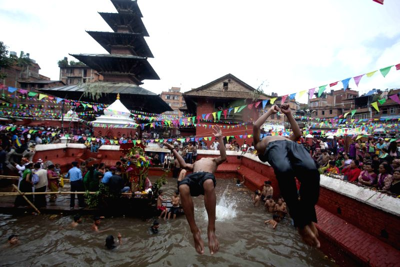 Nepalese youths dive into the holy pond of the Hindu god of destruction during Janai Purnima Festival in Kathmandu, Nepal, Aug. 10, 2014. During the festival, ...