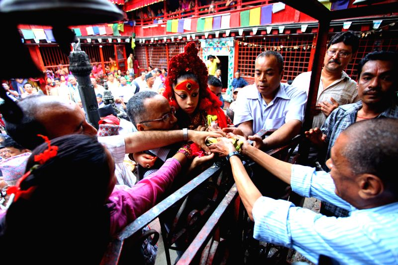 "Nepalese Living Goddess Kumari (C) is carried during the pilgrimage of ""Bahi Dya Byoyegu"", or the visit to Bahals, in Kathmandu, Nepal, Aug. 12, 2014. .."