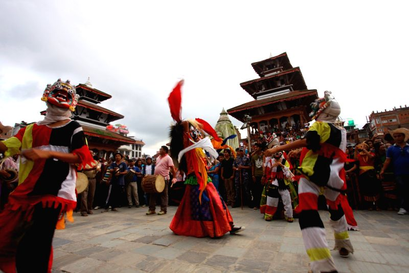 Masked dancers perform during the celebration of Gaijatra at Hanumandhoka in Kathmandu, Nepal, Aug. 16, 2014.