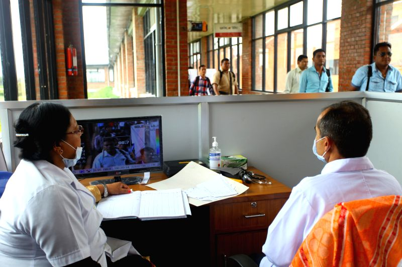 Doctors from Health Service Department, Epidemiology and Disease Control Division monitor passengers at a health desk at Tribhuwan International Airport in view ..
