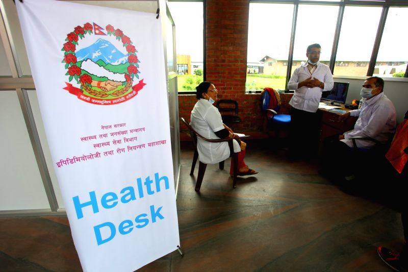 Doctors work at a health desk at Tribhuwan International Airport in view of the outbreak of Ebola Virus Disease in West African nations in Kathmandu, Nepal, Aug. .