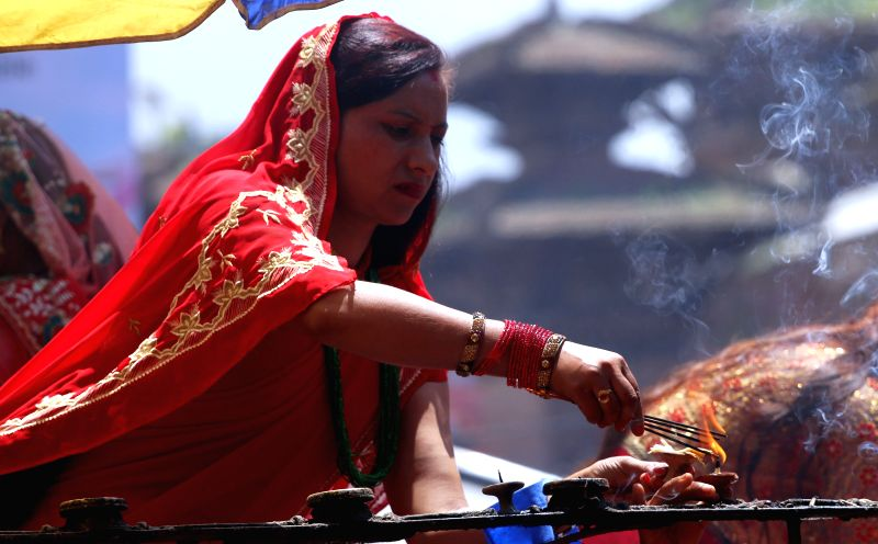 A Hindu woman offers prayers at a Shiva temple during the Teej Festival.