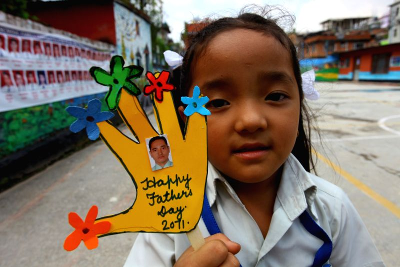 A Nepalese schoolgirl shows a handmade card for her father to celebrate the Kuse Aunsi, or Fathers' Day, in Kathmandu, Nepal, on Aug. 25, 2014. The trandtional ...