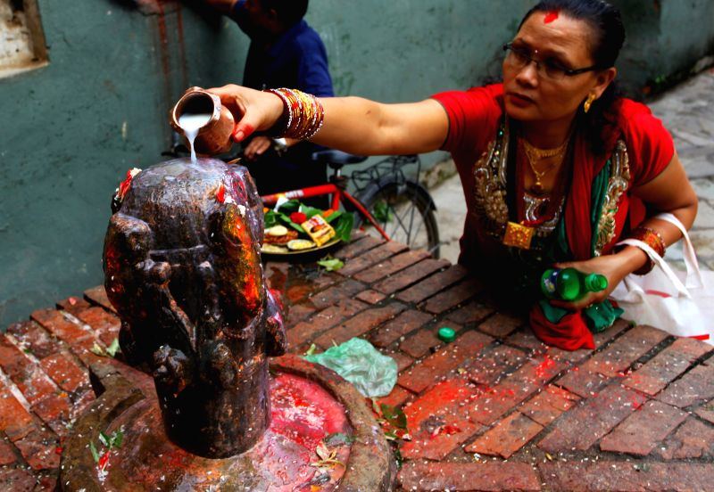A Hindu woman offers milk on the idol of Lord Shiva while offering her prayers during the Teej festival in Kathmandu, Nepal, on Aug 27,2014. During the festival ,