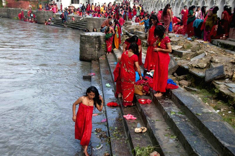 Hindu women take a bathing ritual using Dattiwan, sacred twigs to cleanse themselves and worship at the banks of the Bagmati River on the occasion of the Rishi ...
