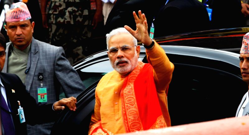 Indian Prime Minister Narendra Modi (C) waves to people after offering his prayers at Pashupatinath temple in Kathmandu, Nepal, Aug. 4, 2014. Indian Prime Minister - Narendra Modi and Inder Kumar Gujral