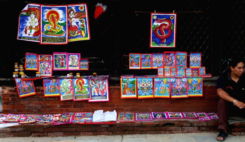 KATHMANDU, Aug. 6, 2016 - A local vendor sells pictures of snake at a market on the eve of Nag-Panchami, a Hindu festival for worshipping the serpent deity, in Kathmandu, Nepal, Aug. 6, 2016. The ...