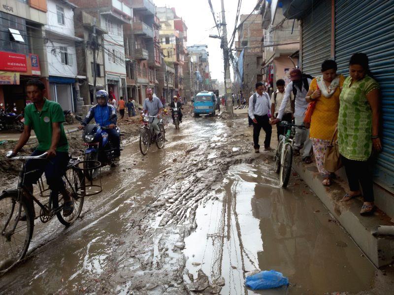 People go across a muddy road after heavy rainfall in Kathmandu, Nepal, Aug. 8, 2014.