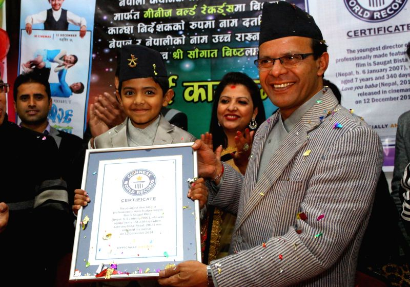 Nepalese eight-year-old kid Saugat Bista (L, front) shows the certificate of Guinness World Records for World's Youngest Director in Kathmandu, Nepal, Feb. 20, ...