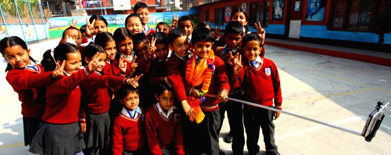 Nepalese eight-year-old kid Saugat Bista (2nd R, front) takes a selfie with his classmates after breaking the Guinness World Records for World's Youngest Director ...