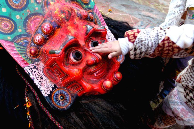 A girl touches the mask of Mahakali Goddess for the Navadurga Dance at Sankhu, northwestern Kathmandu Valley of Nepal, Jan. 9, 2015. Navadurga means nine forms of