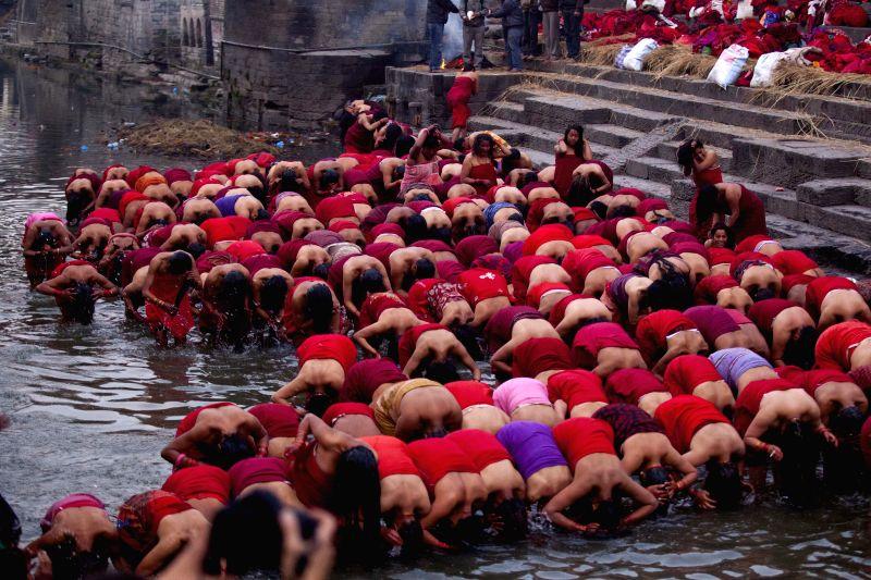 Nepalese Hindu women devotees take a holy dip in the Bagmati River during the Madhav Narayan festival at Pashupatinath in Kathmandu, Nepal, Jan. 20, 2015. ...