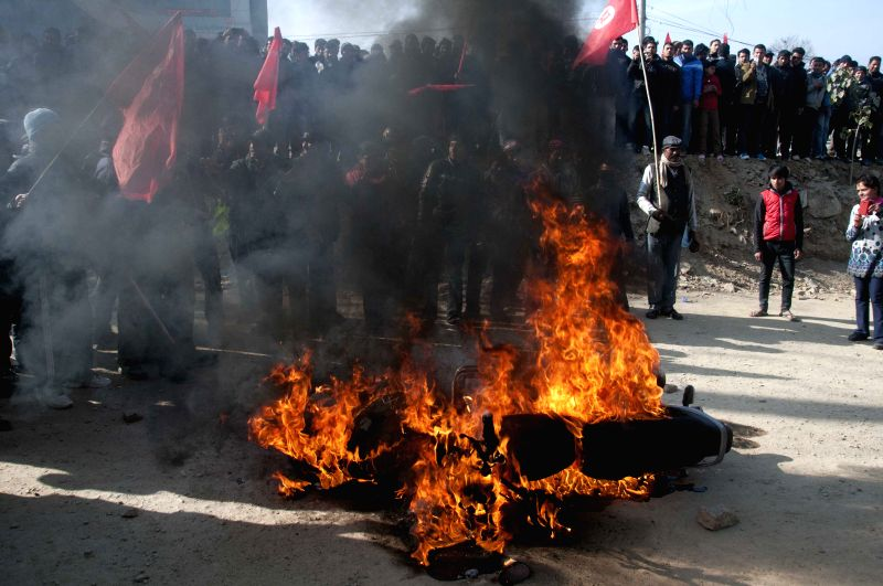 Protesters fire a motorbike during a strike in Kathmandu, Nepal, Jan. 20, 2015. Normal life in many parts across the country has been affected by the strike ...