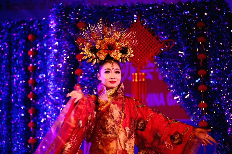 An artist from the Art Troupe of northwest China's Gansu Province presents Happy Chinese New Year performance on the occasion of the 60th anniversary of the ...