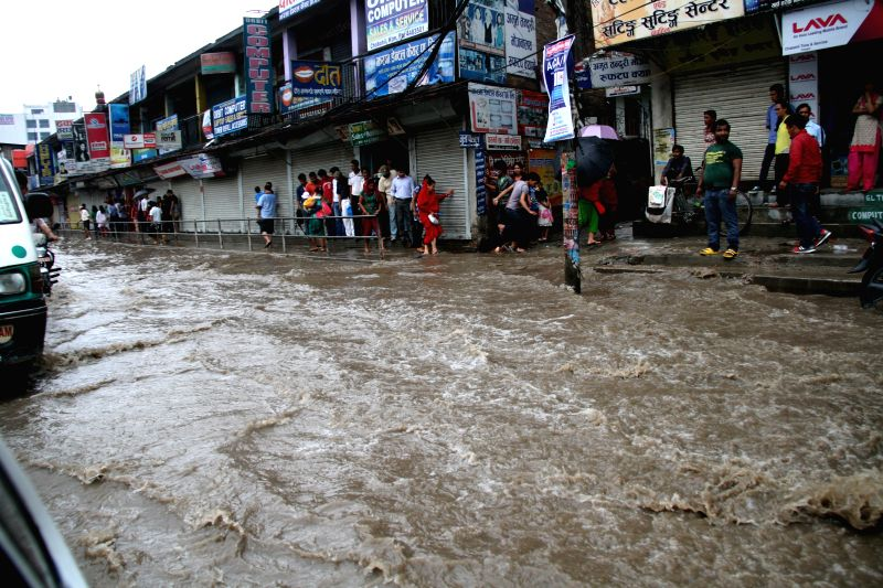 People cross a flooded road after heavy rainfall in Kathmandu, Nepal, July 12, 2014. The monsoon season seems to begin in Nepal from past few days with heavy ...
