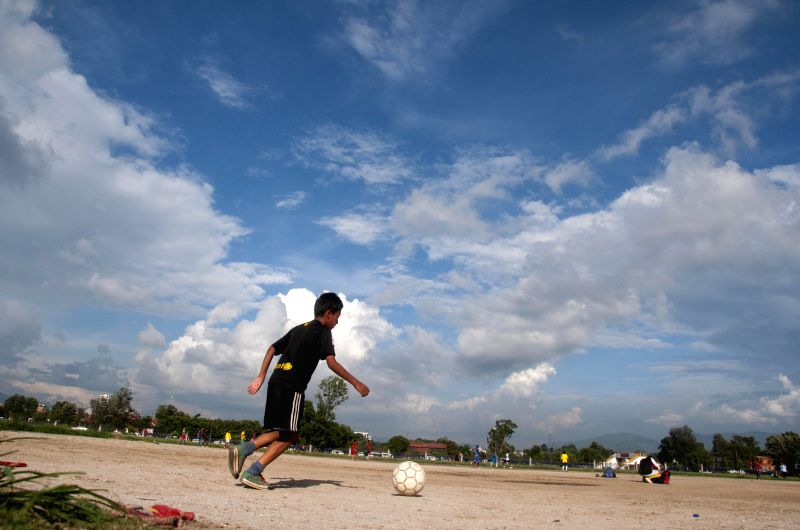 A slum boy plays football at Tundikhel in Kathmandu, Nepal, July 15, 2014.