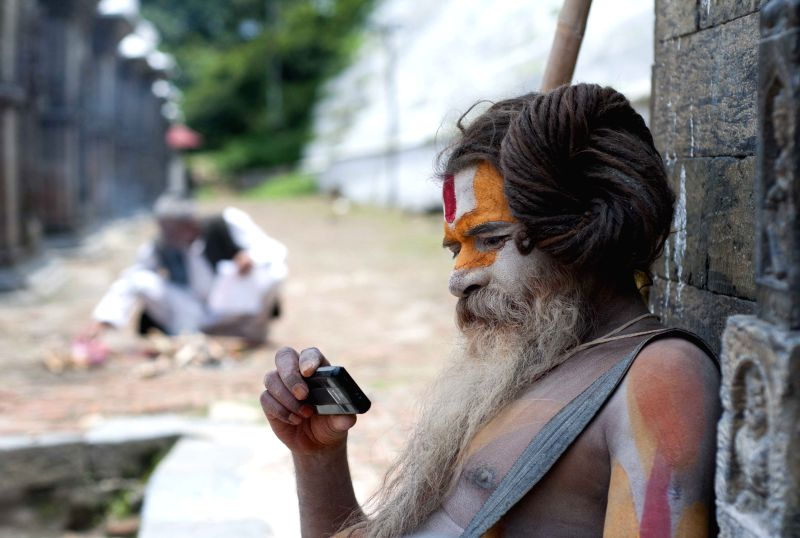 A sadhu or a Hindu holy man, looks at a mobile phone at Pashupatinath Temple in Kathmandu, Nepal, July 1, 2014.
