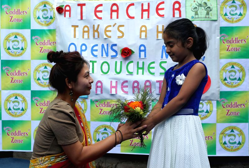 KATHMANDU, July 27, 2018 - A school child offers flowers to her teacher during celebrations of the Teachers' Day at a local school in Kathmandu, Nepal, July 27, 2018.