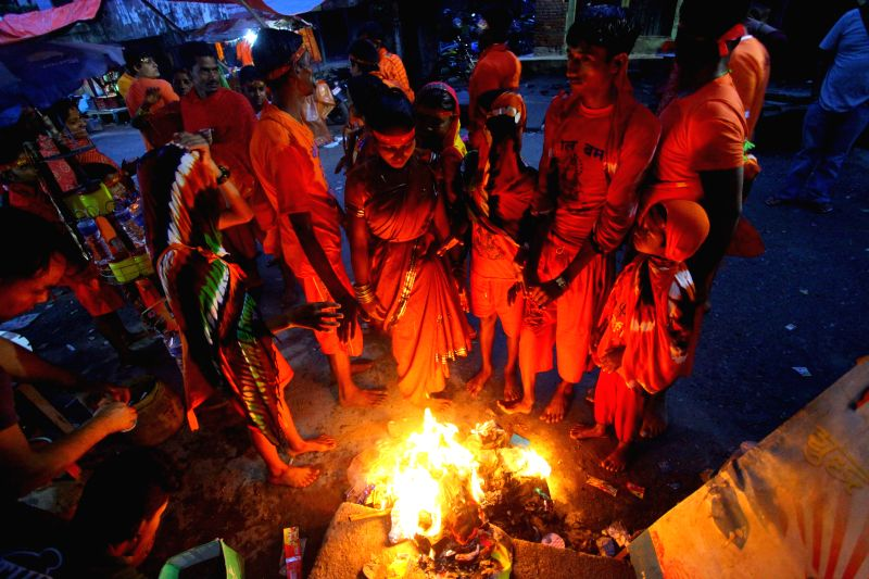 Hindu devotees warm themselves in fire after taking dip and collecting holy water at Sundarijal participating in the ??Bol Bom?? (or Say Shiva) for Shrawan ...