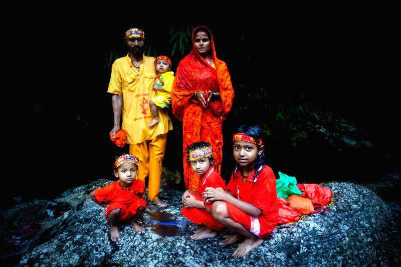 Nepalese Hindu family pose for a photo after collecting water from the Bagmati river during the Bol Bom pilgrimage at Sudarijaal, Katmandu, Nepal, on July 28, ...