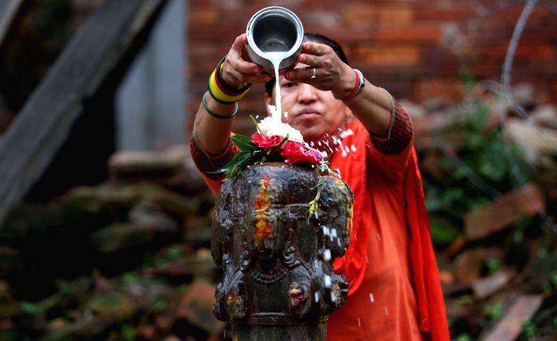 KATHMANDU, July 30, 2018 - A Hindu woman offers milk on the idol of Lord Shiva while offering prayers on Shrawan Somvar at Shiva temple near Hanumandhoka Durbar Square in Kathmandu, Nepal, July 30, ...
