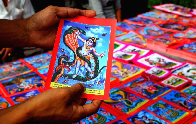 A man selects a picture of a serpent deity in the market on the eve of  the Naag Panchami, a Hindu festival for worshipping the serpent deity, in Kathmandu, ...