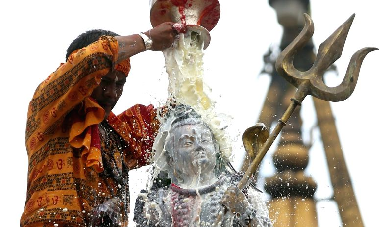 KATHMANDU, July 31, 2018 - A Hindu priest offers milk to the idol of Lord Shiva at the Shiva temple in Kathmandu, Nepal, July 31, 2018. The Shrawan month is considered by Hindus auspicious for ...