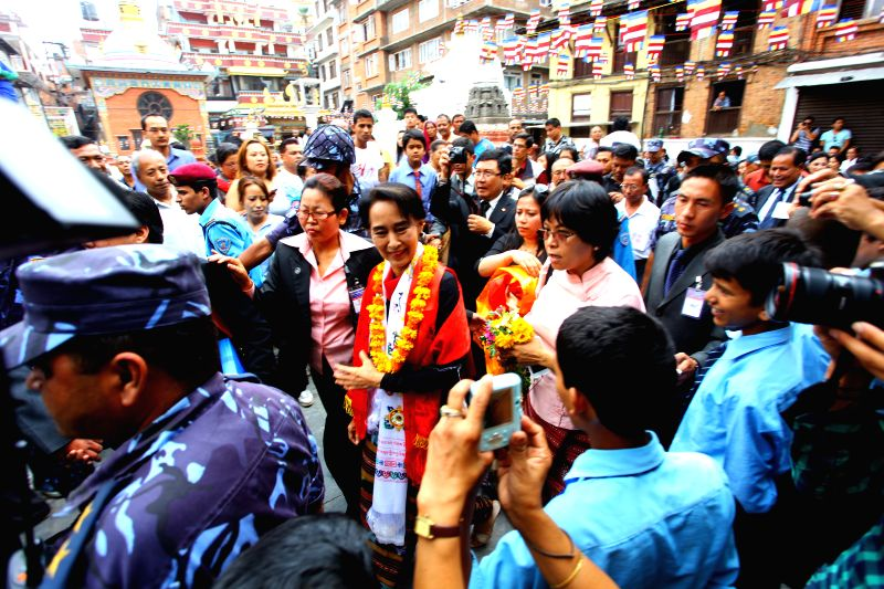 Aung San Suu Kyi, leader of Myanmar's opposition party National League for Democracy, is welcomed by local people at the premises of Dharmakriti Vihar at Naghal ..
