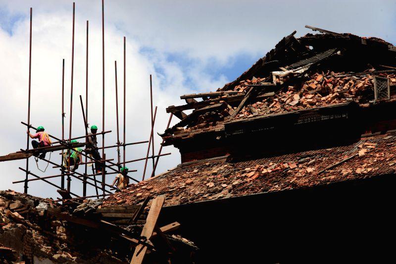 Workers reconstruct Basantapur tower at Hanumandhoka Durbar Square in Kathmandu, Nepal, June 20, 2015. Nepalese government reopened Hanumandhoka Durbar Square, a ...