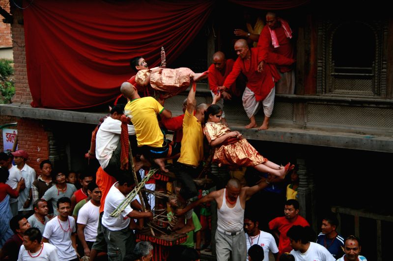 Children are balanced above a prong planted in a chariot to celebrate the Trishul Jatra festival at Jayabageshwori in Kathmandu, Nepal, June 20, 2014. The chariot
