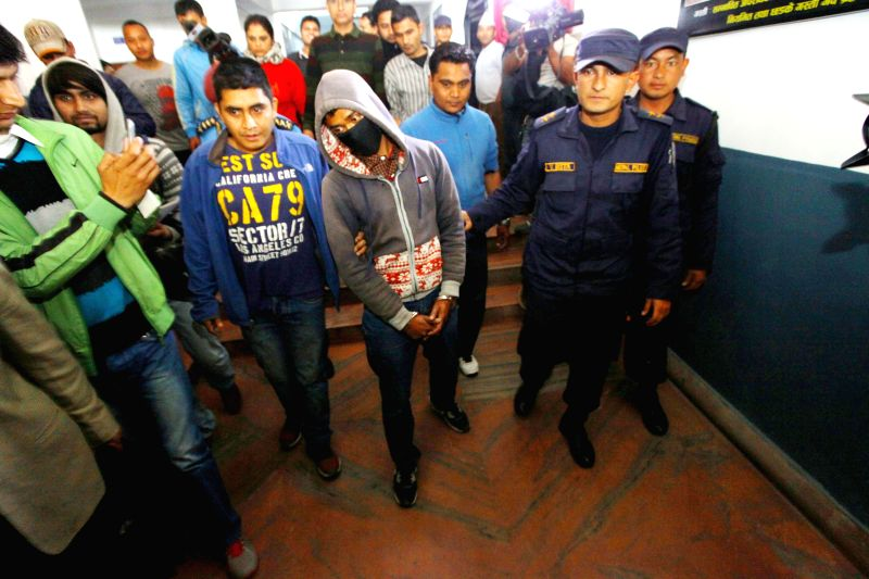 Arrested acid attacker Jivan B.K. (C, front) is brought for a press meeting in Kathmandu, Nepal, March 20, 2015. Two schoolgirls was attacked with acid at a ...