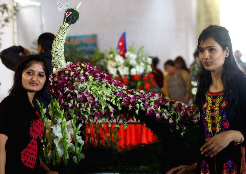Ladies pose for photos with flowers in a shape of peacock during the Flora Expo 2015 at Bhrikutimandap in Kathmandu, Nepal, March 22, 2015. The expo, held from ...