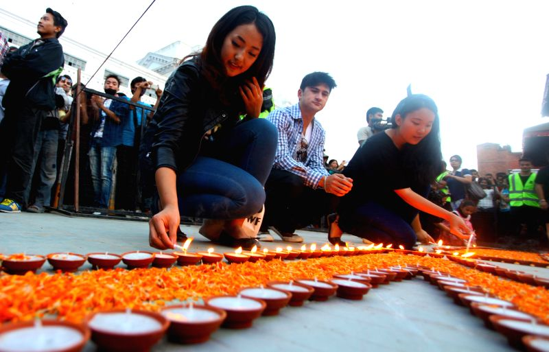 Miss Nepal 2014 Subin Limbu (L, front) lights candles during the annual Earth Hour campaign in Kathmandu, Nepal, March 28, 2015. Earth Hour started as a ...