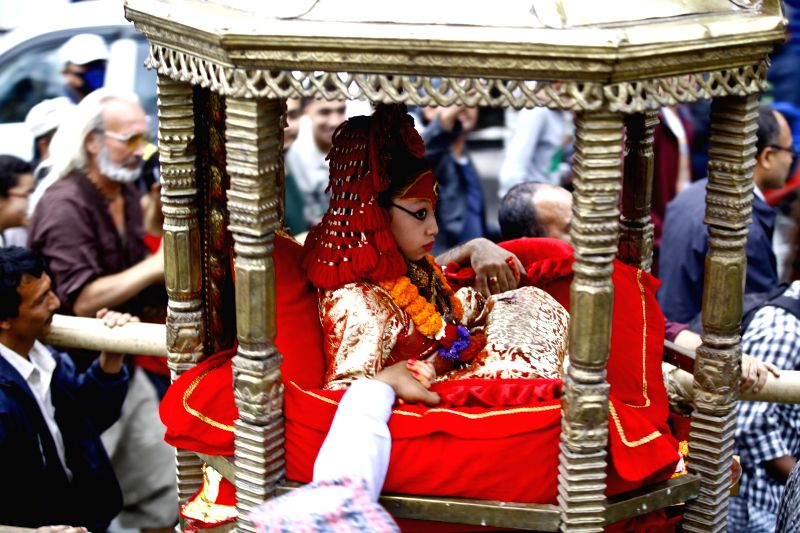 Nepalese Living Goddess Kumari is taken to watch the chariot procession of Lord Seto Machhindranath during a Chariot festival in Kathmandu, Nepal, March 29, ...