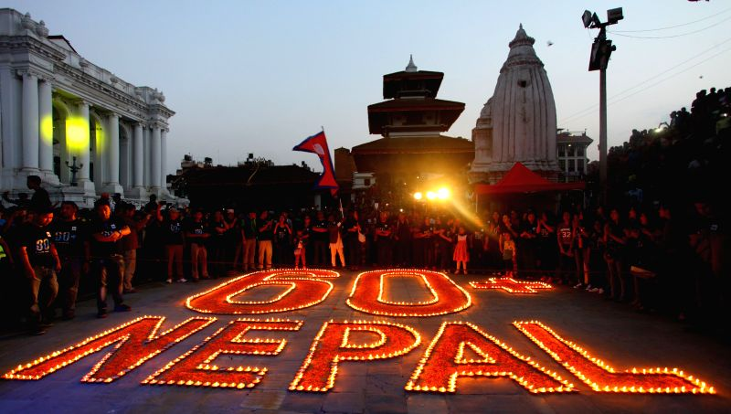 """Nepalese youth gather around the shape of """"60 NEPAL"""" to mark the annual Earth Hour campaign in Kathmandu, Nepal, March 28, 2015. Earth Hour started as ..."""