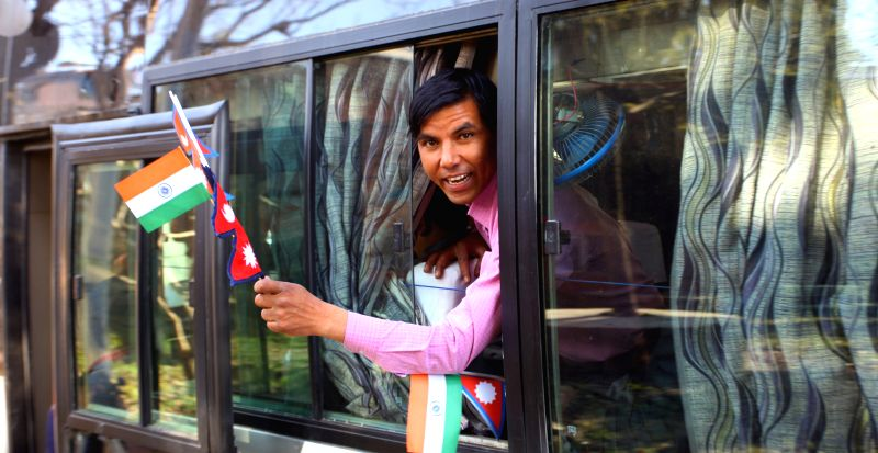 A passenger cheers on a bus proceeding to Banaras during the inauguration of Kathmandu-Banaras bus service in Kathmandu, Nepal, March 5, 2015. The bus service ...
