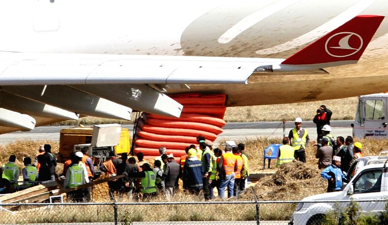 Staff members stand beside the Turkish Airlines Flight TK726 during the process of pushing it back to the runway at Tribhuwan International Airport in Kathmandu, ...