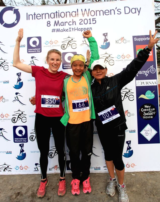 Meera Rai (C), Tori Grieves (L) and Pasi Sherpa pose for photos after winning the first, second and third place respectively in a 5K race organized to mark the ... - Meera Rai