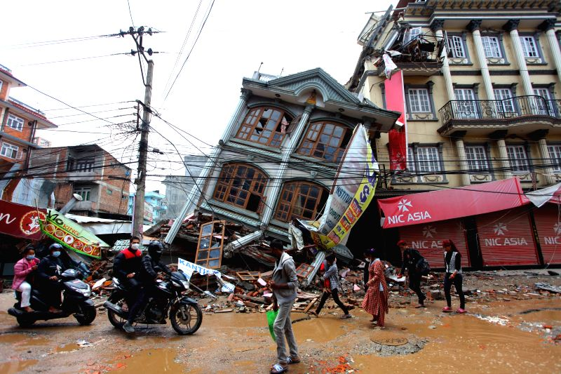 People pass by damaged buildings at Gongabu in Kathmandu, Nepal, April 30, 2015. The death toll from a powerful earthquake in Nepal climbed to 5,844, said the ...