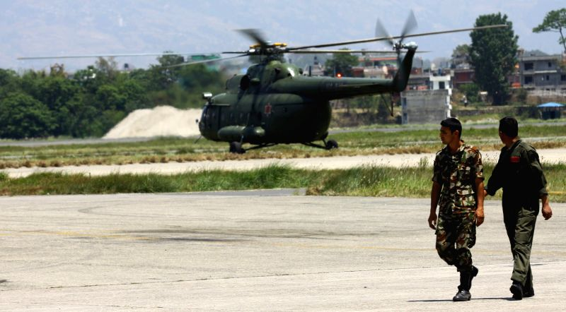 Nepalese Army personnel walk near a landing army helicopter in Kathmandu, Nepal, May 17, 2015. Three bodies had been recovered near the wreckage of a missing U.S. ...