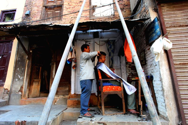 A barber cuts hair for a customer outside a damaged house in Kathmandu, Nepal, May 22, 2015. People in Kathmandu are having a hard time not getting a haircut due ...