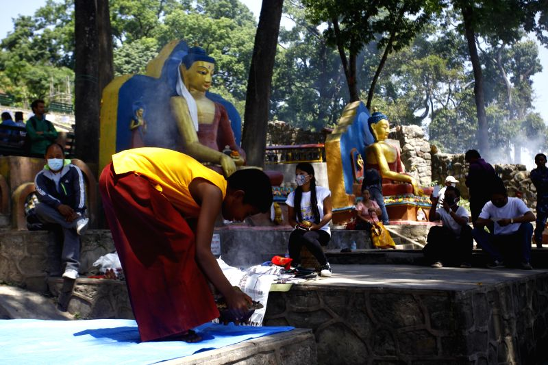 """A Buddhist monk offers prayers during Buddha Jayanti festival in Kathmandu, Nepal, May 4, 2015. Buddha Jayanti, sometimes informally called """"Buddha's ..."""