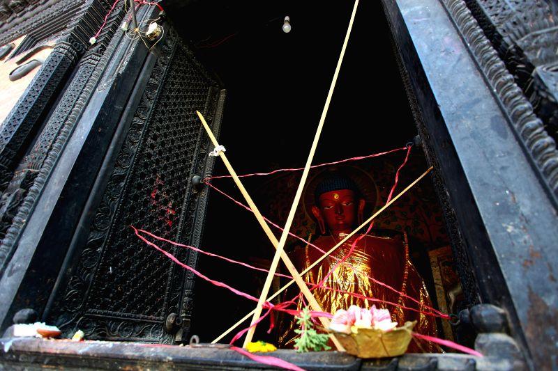 Photo taken on May 4, 2015 shows offerings to idol of Buddha during Buddha Jayanti festival at quake-wracked monastery in Kathmandu, Nepal. People visited Buddhist ...